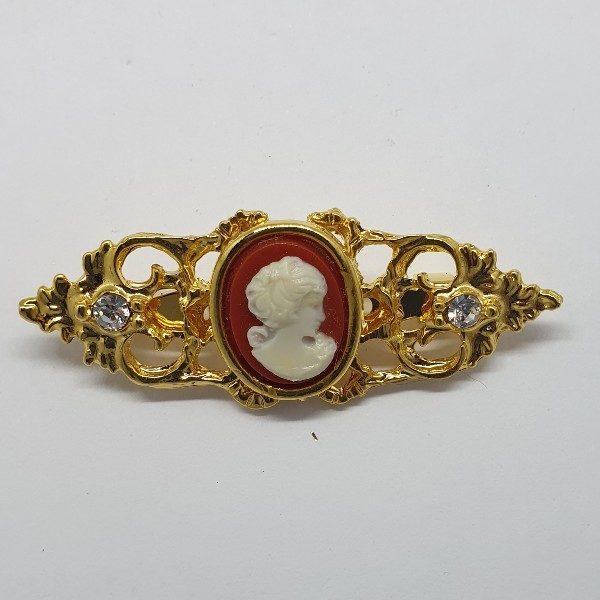 Broche alargado con camafeo blanco roto y filigrana en dorado