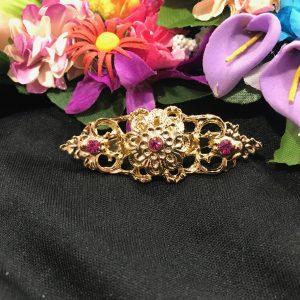 Broche huertana alargado en dorado con flor en relieve y piedras de color para combinar con tu mantón