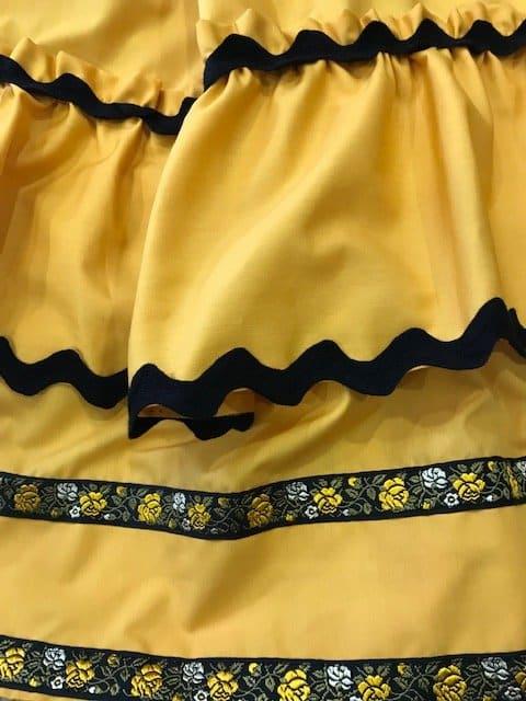 Zagalejo amarillo de señora con piculinas y tiras bordadas haciendo juego
