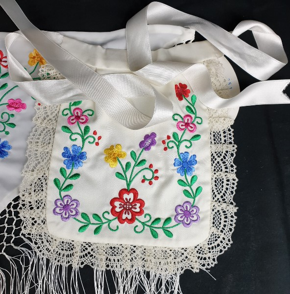 Pico y delantal bordado para bebe de huertana en color beige bordado en flores de colores