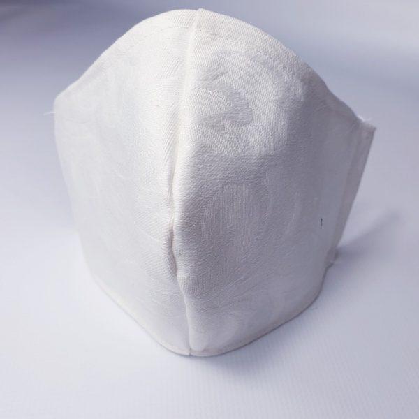 Mascarilla de tela relieve en color blanco lavable y reutilizable con filtro desechable incluido